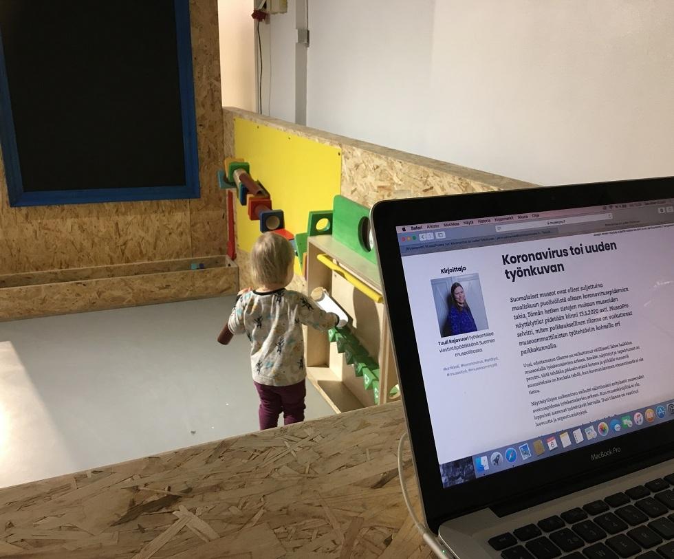 Pieni lapsi leikkimässä museokohteella, ja läppärin ruutu, jossa Korona-aiheinen otsikko.